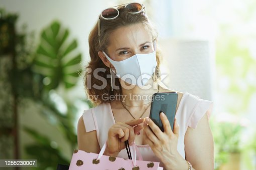 Life during covid-19 pandemic. young woman shopper in pink blouse with medical mask, paper shopping bags and smartphone making online shopping on e-commerce site.
