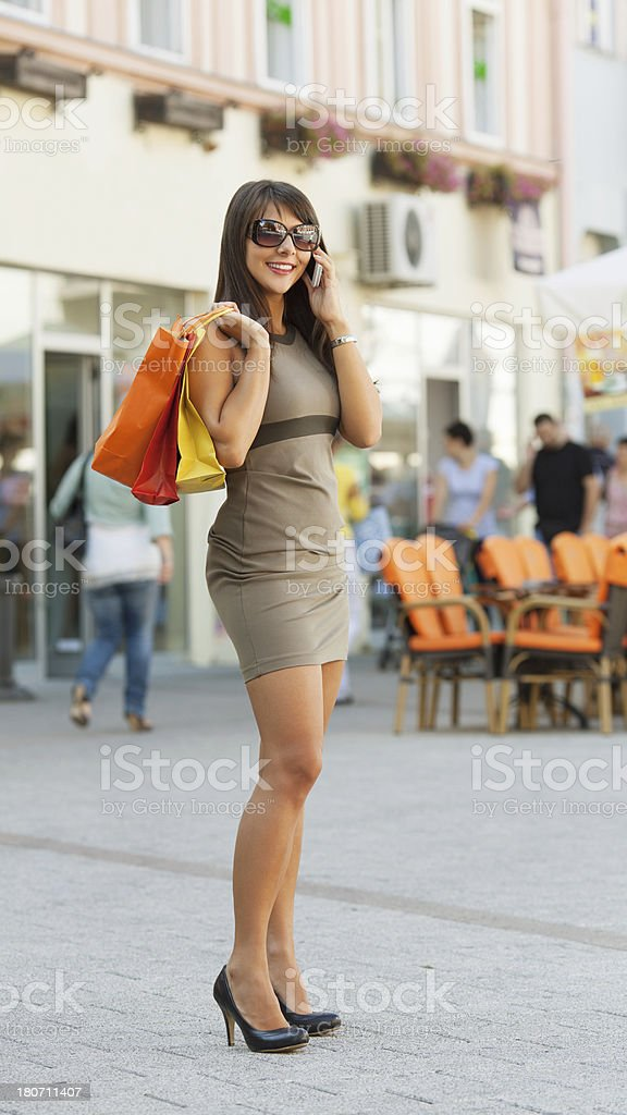 Woman shopping and talking on the phone royalty-free stock photo