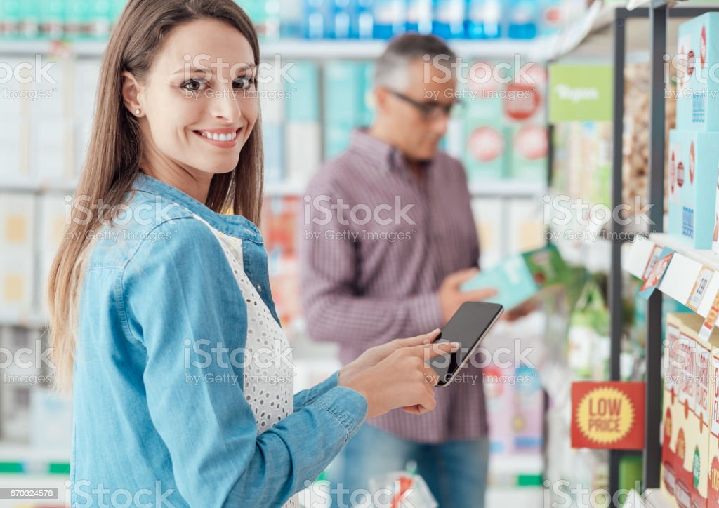 Woman shopping and using her phone stock photo