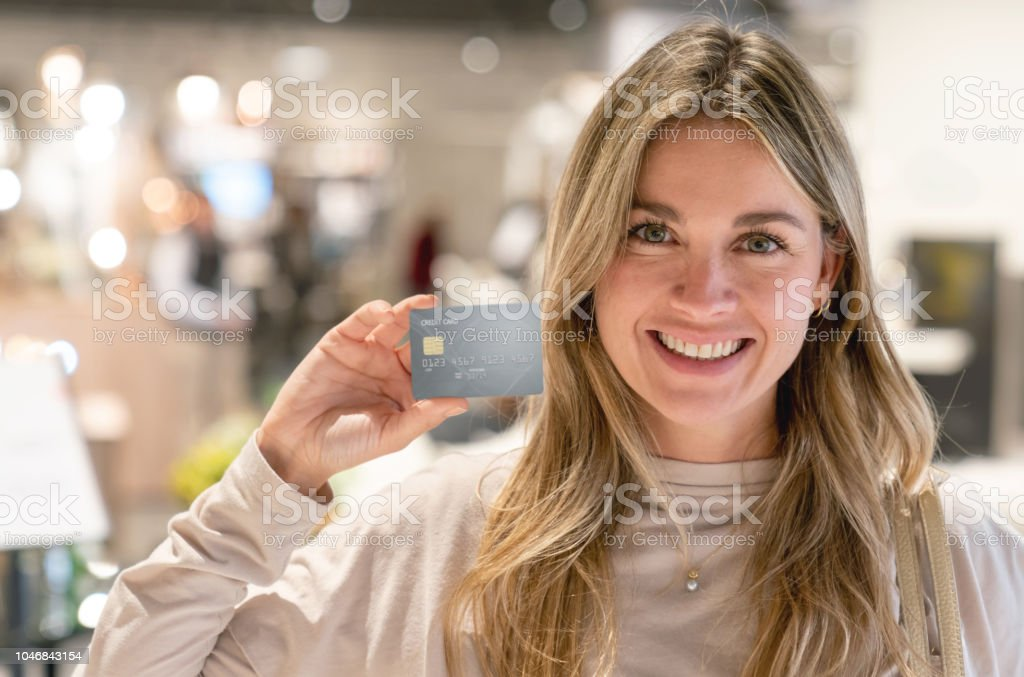 Happy woman shopping at a furniture store using a credit card and...