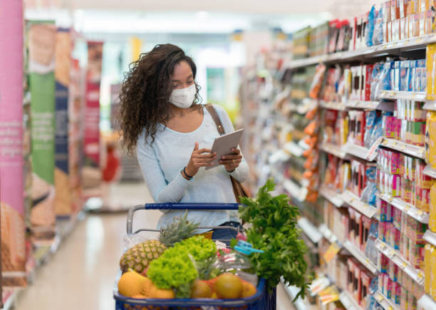 Woman shopping at the grocery store wearing a facemask stock photo