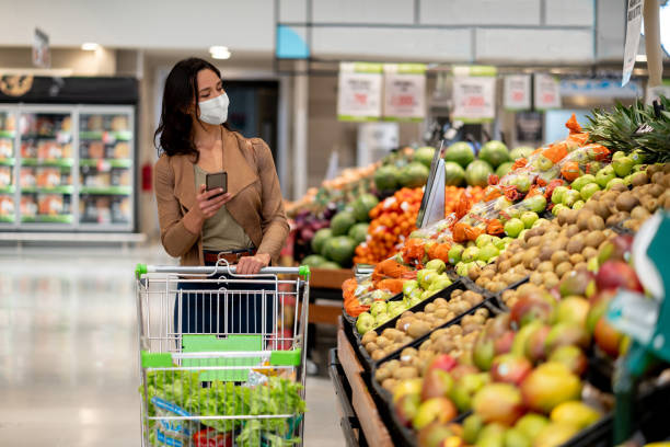 Woman shopping at the grocery store wearing a facemask Woman shopping at the grocery store wearing a facemask to avoid the coronavirus while following a list on her cell phone - COVID-19 lifestyle concepts supermarket stock pictures, royalty-free photos & images