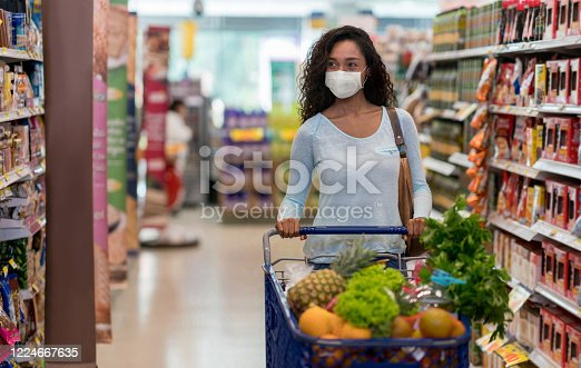 istock Woman shopping at the supermarket wearing a facemask 1224667635