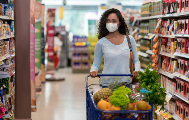 Woman shopping at the supermarket wearing a facemask stock photo