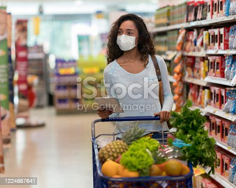 Woman shopping at the supermarket wearing a facemask to avoid the coronavirus while following a list on her tablet computer – COVID-19 lifestyle concepts