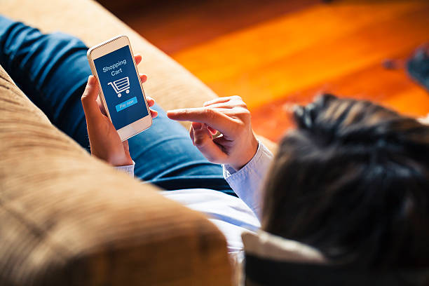 woman shopping by mobile phone laying at home. blue screen. - app store stock photos and pictures