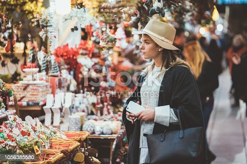 Young woman choosing gifts at the Christmas market