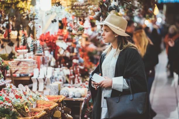 vrouw winkelen kerst presenteert - marktkraam stockfoto's en -beelden