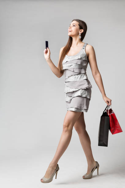 Woman Shopping Dress with Credit Card and Paper Bags, Fashion Model Full Length Studio Portrait, Girl Going to buy clothing stock photo