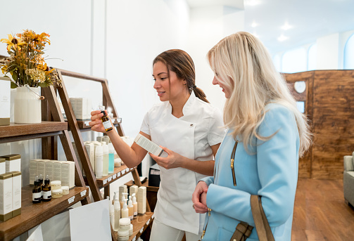 Happy woman shopping for beauty products at a store or a spa and talking to the saleswoman