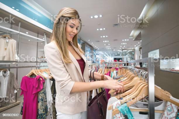 Woman Shopping For Clothes At A Clothing Store - Fotografias de stock e mais imagens de 20-29 Anos