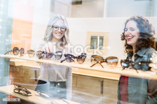 A saleswoman or optometrist helps a customer try on different eyeglass frames at an eyecare storefront.  They select different frames and styles looking for an ideal fit.