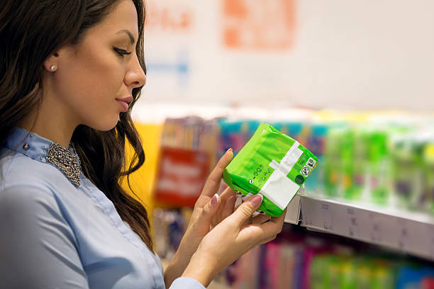 woman shopping for sanitary pad - sanitary pad stock photos and pictures