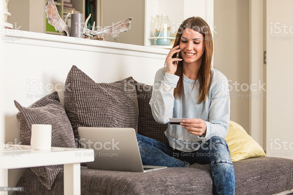 Woman shopping from home, talking on the mobile phone stock photo