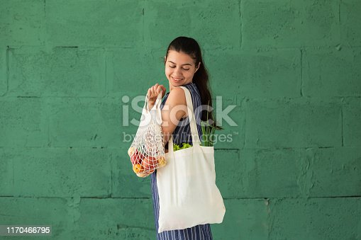 Woman shopping fruits and vegetables with reusable cotton Eco produce bag. Zero waste lifestyle concept