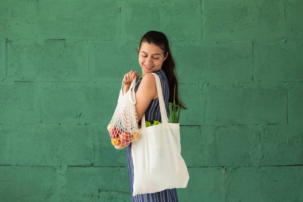 woman shopping fruits and vegetables with reusable cotton eco produce bag. zero waste lifestyle concept - vacations food stock pictures, royalty-free photos & images