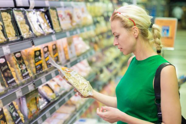 frau einkaufen lebensmittel im supermarkt. - bio lebensmittel stock-fotos und bilder