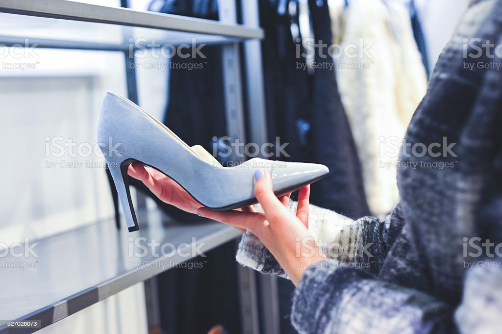 Woman shopping high heel shoes in a store stock photo