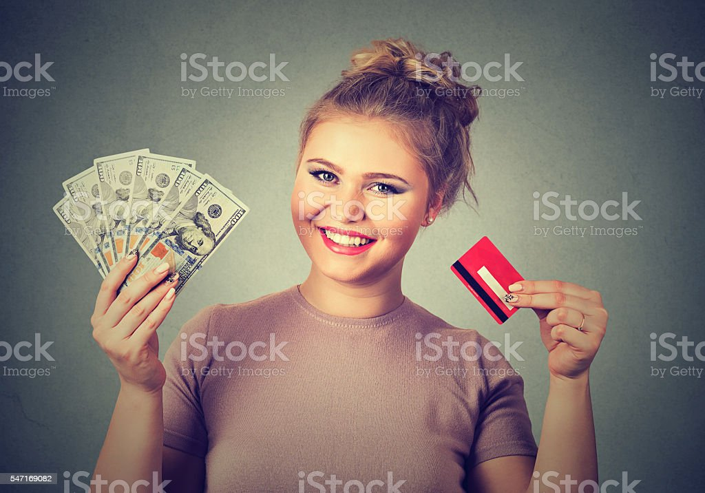 woman shopping holding credit card cash dollar bills stock photo
