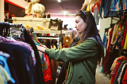 Vintage toned portrait of a young beautiful brunette woman in London second hand marketplace. She is wearing casual Autumn clothes, an olive green parka jacket, browsing through the stuff in the market.