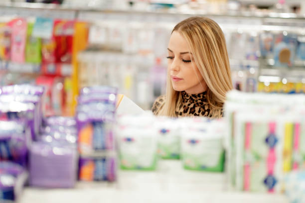 Woman shopping in pharmacy Blonde woman shopping in pharmacy, copy space tampon stock pictures, royalty-free photos & images