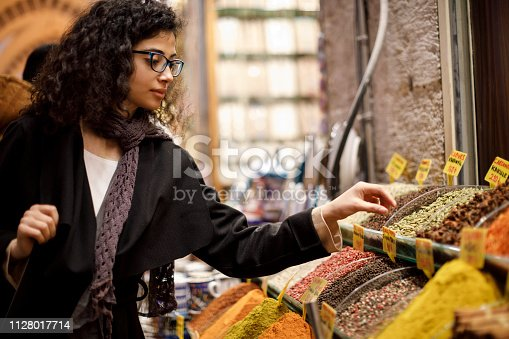 Woman shopping in spice shop in Grand Bazaar, Istanbul, Turkey