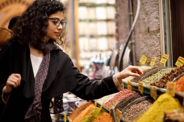 donna che fa shopping nel negozio di spezie nel grand bazaar, istanbul, turchia - bazar mercato foto e immagini stock