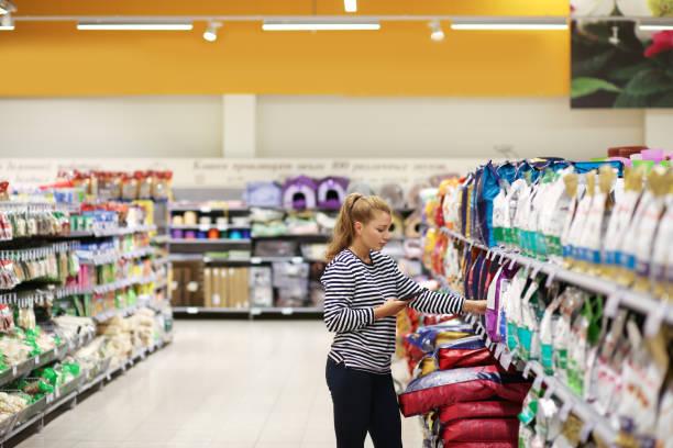 woman shopping in supermarket reading product information. pet food. - dog food imagens e fotografias de stock