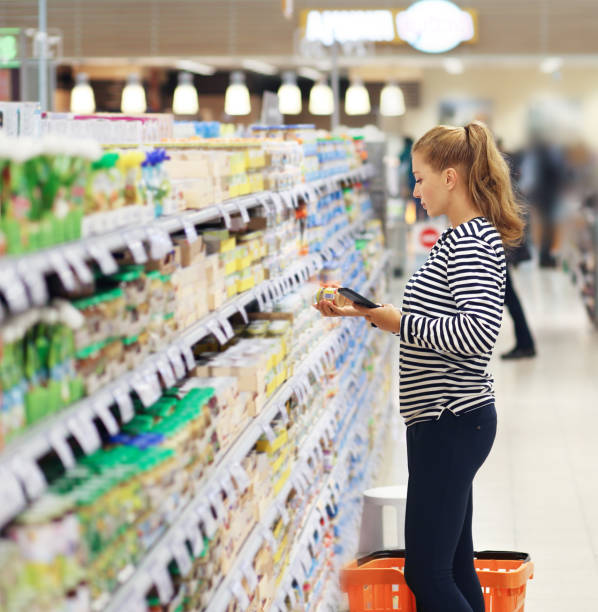 woman shopping in supermarket reading product information. - consumer products stock pictures, royalty-free photos & images