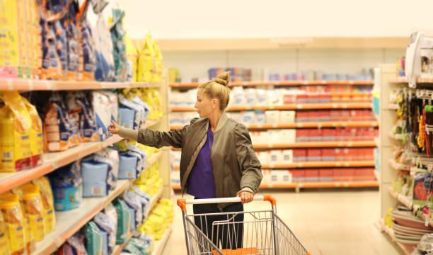 frau einkauf im supermarkt produktinformationen lesen. - grundnahrungsmittel stock-fotos und bilder
