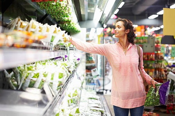 Woman shopping in the produce section of the market stock photo
