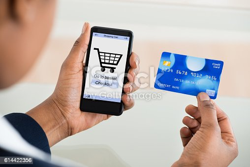 Close-up Of A Woman Using Card While Shopping On Mobile Phone