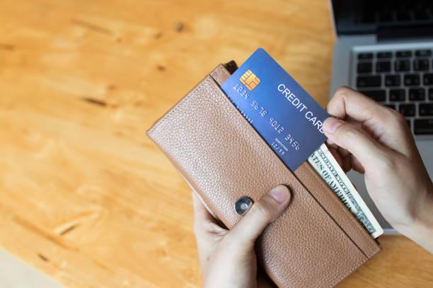 frau online einkaufen und bezahlen mit einer kreditkarte aus der brieftasche. kopieren sie raum. - kreditkarten stock-fotos und bilder
