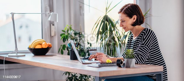 istock Woman shopping online and using credit card 1144320617