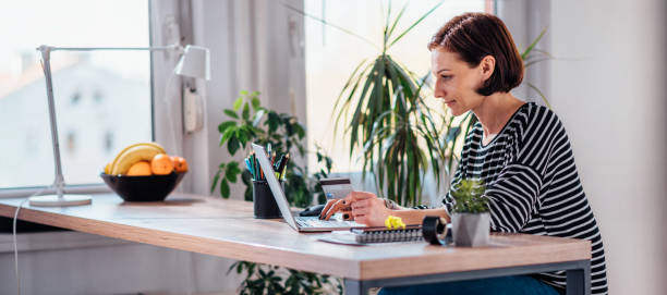 Woman shopping online and using credit card Woman using laptop and shopping online while holding credit card at the desk by the window home shopping stock pictures, royalty-free photos & images