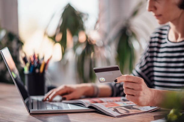 woman online winkelen en het gebruik van creditcard - woman home magazine stockfoto's en -beelden