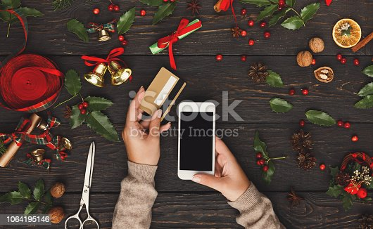 istock Woman shopping online for christmas on smartphone 1064195146