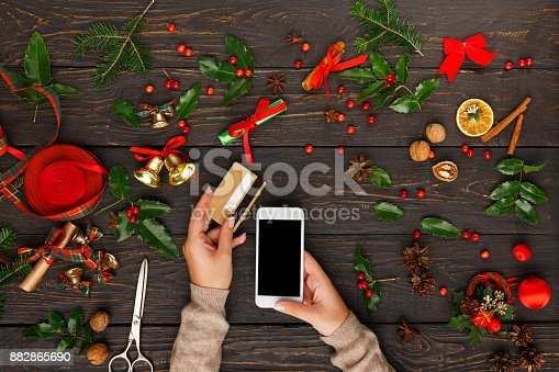 istock Woman shopping online for christmas on smartphone 882865690