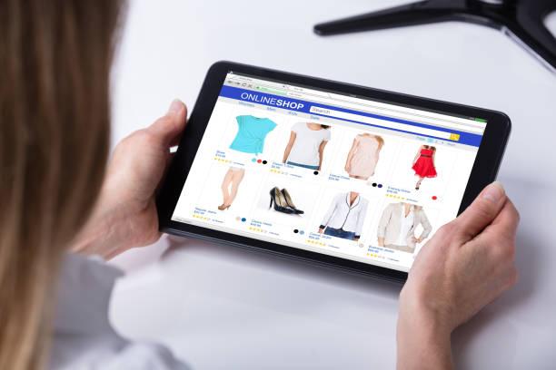 frau online-shopping auf tablet pc - kleider günstig kaufen stock-fotos und bilder
