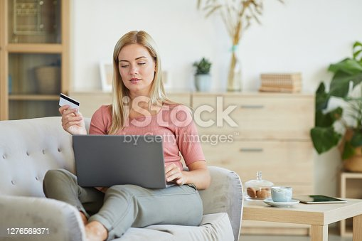 Young woman lying on the sofa with laptop and using credit card for online shopping at home