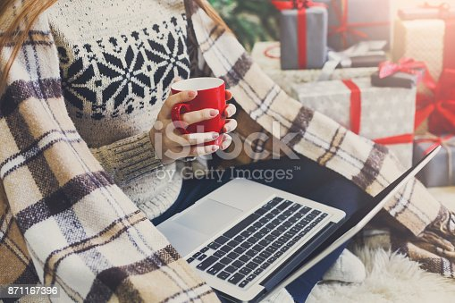 Christmas online shopping. Woman has coffee, buy presents on laptop, prepare to xmas, among gift boxes and packages. Winter sales