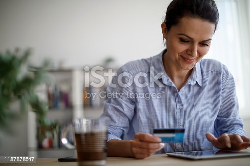 1150572102istockphoto Woman shopping online using digital tablet and credit card 1187878547