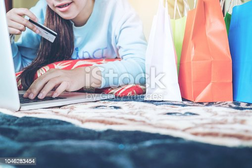 613550706 istock photo woman shopping online using laptop enjoying in home 1046283454