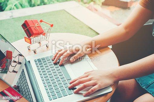 613550706 istock photo Woman shopping online using laptop with credit card enjoying 856804484