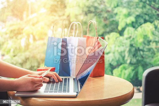 613550706 istock photo Woman shopping online using laptop with credit card enjoying 962735056