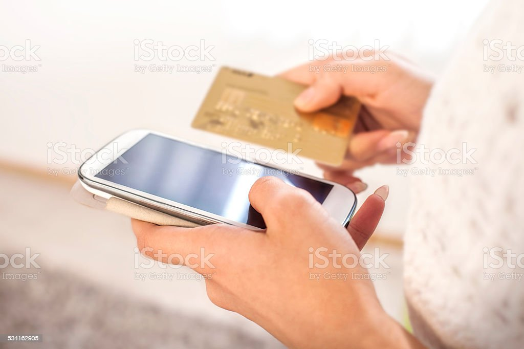 a659a2bf78f Woman shopping online using mobile phone and credit card royalty-free stock  photo