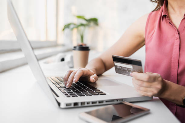 Woman shopping online with laptop and credit card stock photo
