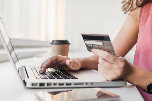 woman shopping online with laptop and credit card - spending money stock pictures, royalty-free photos & images