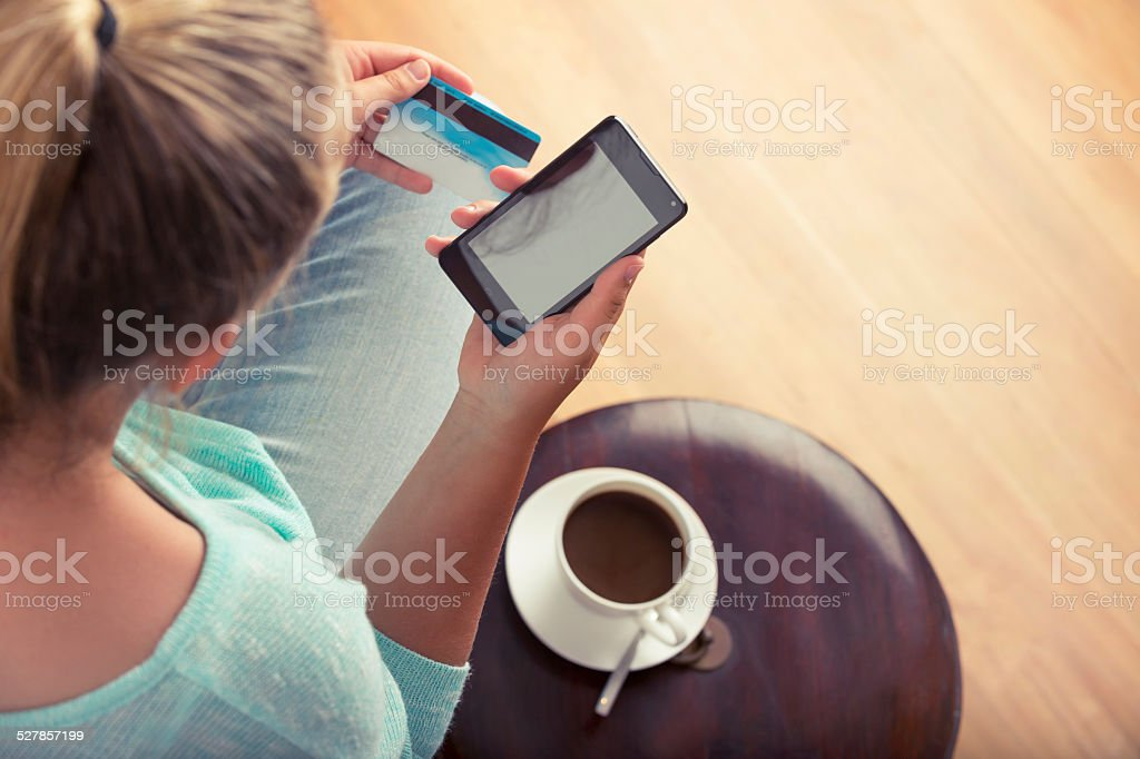 Woman shopping online with mobile phone and credit card. stock photo