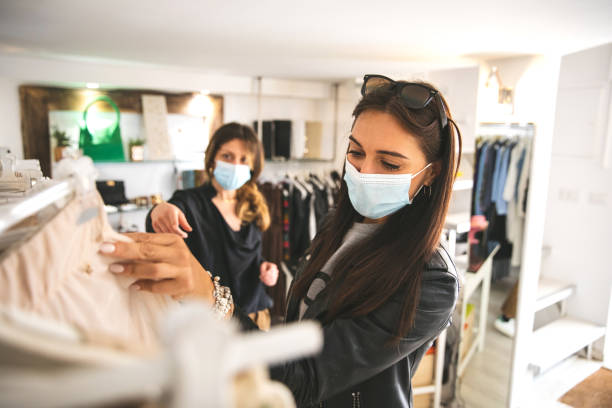 Woman shopping protecting herself wearing protective mask Woman shopping protecting herself wearing protective mask boutique stock pictures, royalty-free photos & images